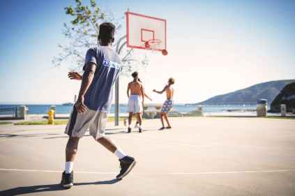 four people playing basketball